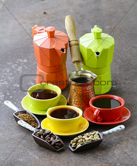 green, black coffee beans and different utensils for boiling coffee (grinder, kettle, cezve)