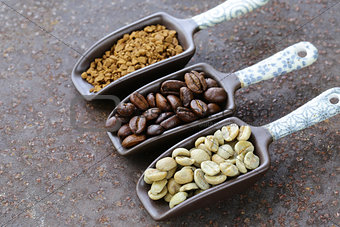 green, black coffee beans and ground in the scoop