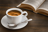 coffee on dark table with book