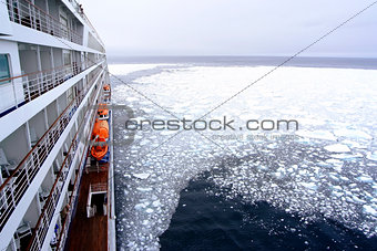 Cruise Ship bow passing icy snow arctic waters near Spitsbergen, Svalbard, Norway.