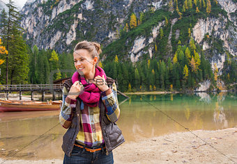 Portrait of smiling woman on Lake Bries readjusting scarf