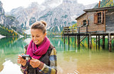 Woman on the shores of Lake Bries checking photo on camera