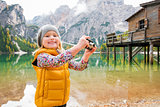 Young blonde girl smiling at Lake Bries and playing with camera