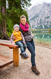 Mother and daughter resting at wooden picnic table on Lake Bries