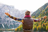Woman hiker opening arms in joy against autumn background