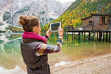 Woman at Lake Bries taking scenic photo with digital tablet