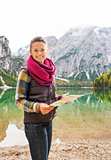 Smiling woman hiker holding map on the shores of Lake Bries