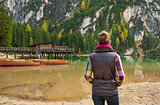 Woman hiker looking out at wooden boats and pier on Lake Bries