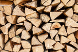 Background of chopped firewood stacked up on top of each other