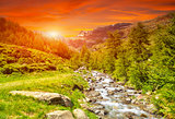 Colorful sunset and a river in the Alps