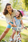 Laughing mother and daughter learning how to ride a bike