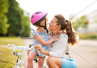 Blonde girl in pink helmet gives Eskimo kisses to her mother