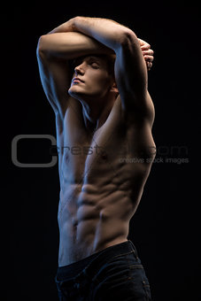 Portrait of handsome red-haired athlete topless at the studio