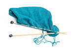 blue yarn with knitted fabric and knitting needles