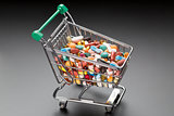Shop cart with different colorful pills on black