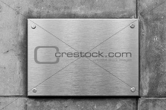 blank metal sign or nameboard on concrete wall