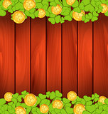 Clovers and golden coins on brown wooden background for St. Patr