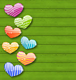 Multicolored striped hearts on green wooden texture for Valentin