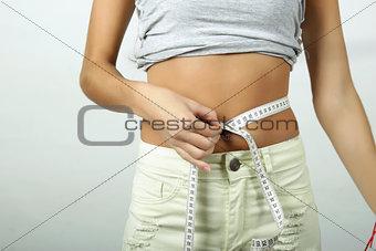 Slim girl measuring her waist.