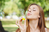 young woman blowing soap bubbles in the air.