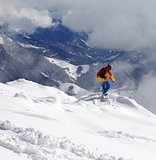 Snowboarder on off-piste slope an mountains in haze