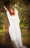 Charming redhead woman wearing white dress stands near tree