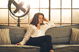 Elegant woman sitting on a sofa, crossing legs, in a loft