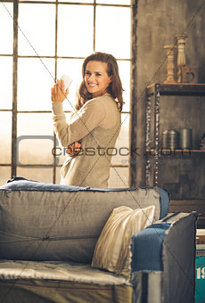 Casually-dressed woman standing in loft by sofa holding phone