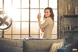 Looking back, a brunette is smiling standing by a loft window