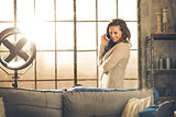 Smiling brunette in loft stands talking on the phone behind sofa