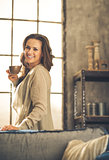Brunette holding cup of coffee while smiling in loft apartment