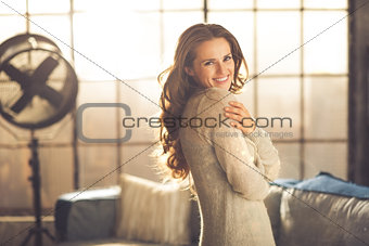 Casual brunette hugging herself while smiling in loft apartment