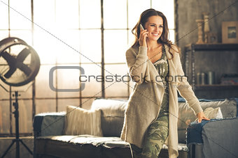 Smiling brunette on phone in chic urban loft apartment