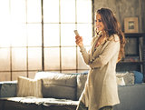 Woman looking away holding phone standing in loft apartment