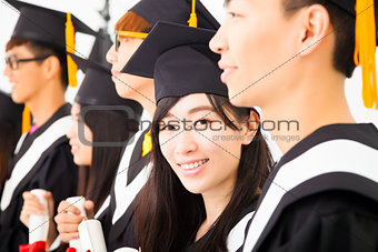 asian female college graduate at graduation with classmates