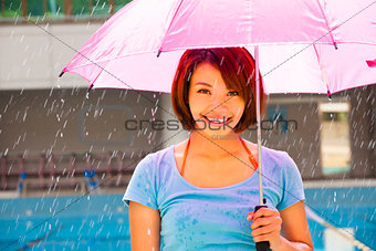 Beautiful young woman under pink umbrella