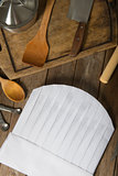 Chef hat and wooden spoons on wooden table