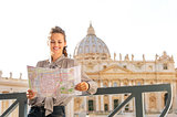 Smiling woman tourist in Vatican City in Rome reading a map