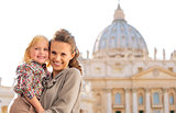 Smiling mother and daughter cheek to cheek in Vatican City Rome