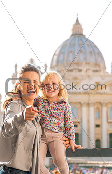 At the Vatican in Rome, laughing mother holds child and points