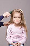 Hairdresser brushing her long hair girls
