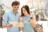 Couple of tourists consulting a city guide and mobile gps
