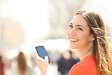 Happy woman walking in the street using a smartphone