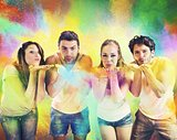Friends blowing colored powders