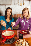 Two friends eating fondue