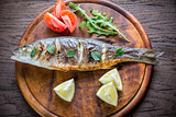 Grilled seabass with lemon on the wooden board