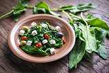Spinach with cheese, olives and pepper drops