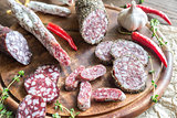 Slices of saucisson and fuet on the wooden board