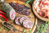 Slices of saucisson, jamon and basturma on the wooden board