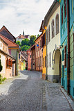 Stone paved old street with colored houses from Sighisoara fortr